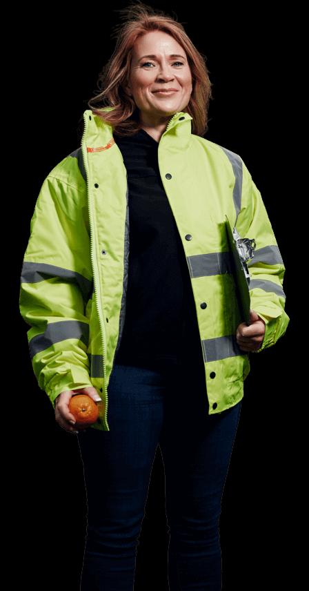 Lächelnde rothaarige Frau in gelber Warnschutzjacke mit Klemmbrett unter dem linken Arm und einer Orange in der rechten Hand