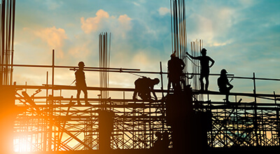 Scaffolding at sunrise, people working
