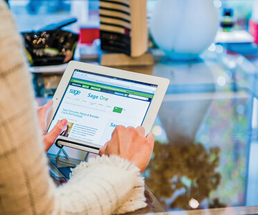 Woman using a tablet at a glass shop counter