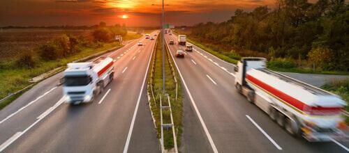 Camions roulant sur des voies opposées sur une autoroute très fréquentée au coucher du soleil
