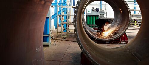 Personne portant une combinaison et des équipements de sécurité en train de souder un énorme tuyau en métal dans une usine